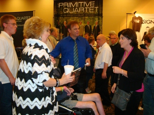 Paul with Jeff and Sheri Easter with guests at their booth